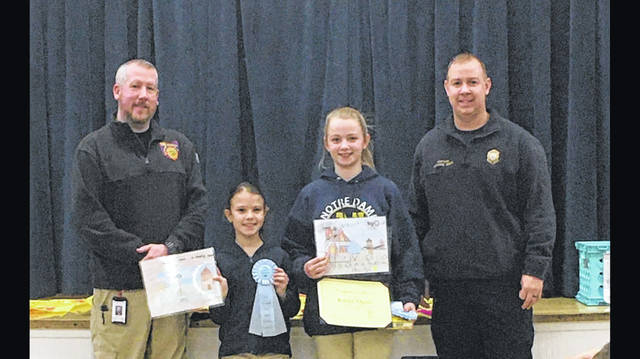 Left to Right: State Fire Prevention Officer, Paul Martin with Notre Dame Students Finley Noel and Kailee Ogier, and Michael Sines the Fire Prevention Officer for the City of Portsmouth at the assembly for the girls winning the State Fire Posters.