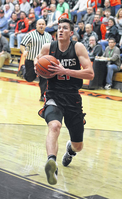 Wheelersburg's Carter McCorkle (21) charges in for a layup during the Pirates' Southern Ohio Conference Division II boys basketball game against host Waverly on Thursday night.