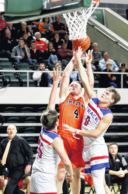 Ironton senior Gage Salyers (4) shoots over Zane Trace defenders Colby Swain (0) and Carter Hill (25) during Friday night's Division III boys basketball district championship game at the Ohio University Convocation Center.