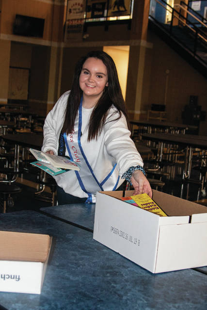 Miss Clay 2020 and Clay Local Schools student Bailey Gillispie sorts through donated books to be distributed to students.