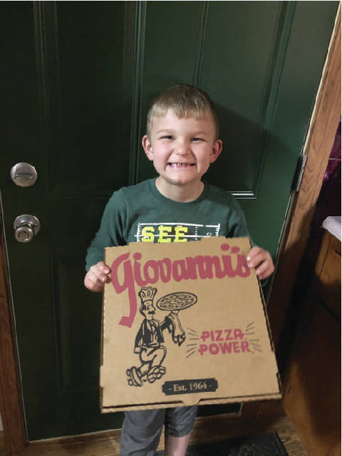 1st grade student Lucas Kamer answered the door to a pizza with his name on it.