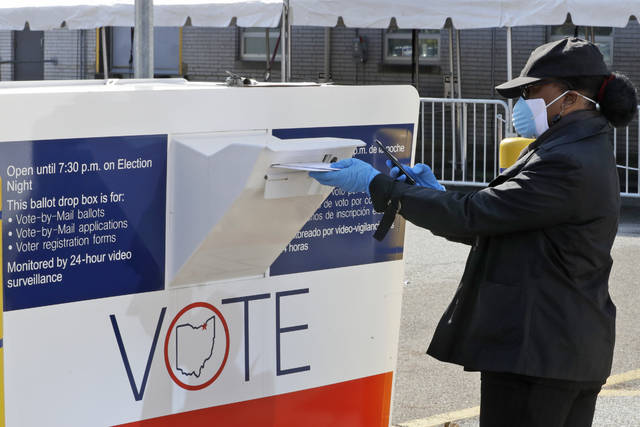 Marcia McCoy drops her ballot into a box outside the Cuyahoga County Board of Elections, Tuesday, April 28, 2020, in Cleveland, Ohio. The first major test of an almost completely vote-by-mail election during a pandemic is unfolding Tuesday in Ohio, offering lessons to other states about how to conduct one of the most basic acts of democracy amid a health crisis. (AP Photo/Tony Dejak)