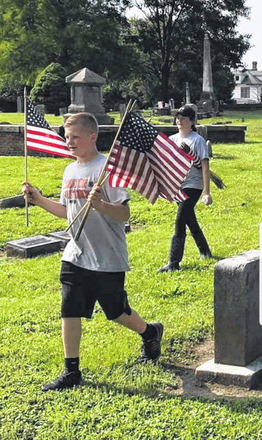 Members of the Senators 4-H Livestock Club place flags on the graves of veterans at Greenlawn Cemetery a year ago.