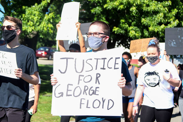 A protester holding a sign that says justice for George Floyd as he marched down Second Street Sunday evening.