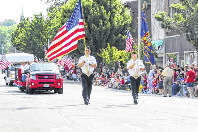 Two members of the United States Armed Forces carry flags to lead the Ironton-Lawrence County Memorial Day Parade in a previous year.