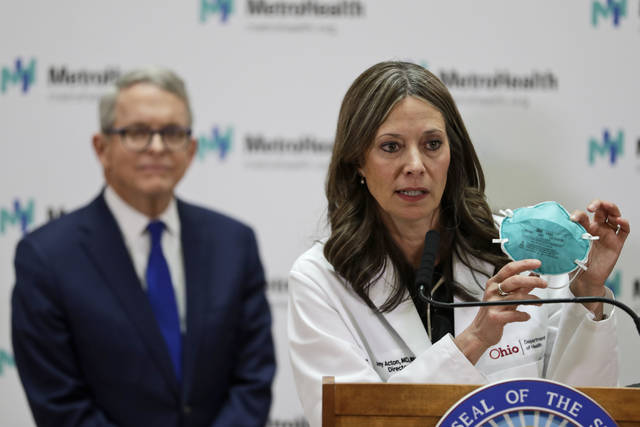 "FILE - In this Feb. 27, 2020 file photo Ohio Department of Health Director Amy Acton speaks during a news conference at the MetroHealth Medical Center in Cleveland. Ohio Gov. Mike DeWine, left, watches. Under pressure from law enforcement, Tennessee's top health officials quietly agreed in April to release the names and addresses of those who had been treated or exposed to COVID-19 to police departments and sheriff's offices. Acton issued an order April 24 requiring local health departments to provide emergency dispatchers the names and addresses of people within their jurisdictions who tested positive. The order required dispatchers to treat the data as ""protected health information"" and to remove it from the system once a person has recovered from the illness, although the order is unclear on how dispatching agencies would learn of this follow-up information. (AP Photo/Tony Dejak, file)"