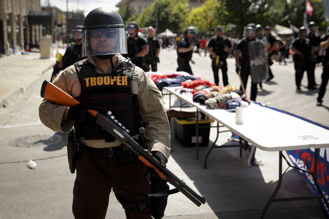 "FILE - In this June 20, 2020, file photo a trooper stands outside the BOK Center where President Trump will hold a campaign rally in Tulsa, Okla. In law enforcement, they're referred to as ""non-lethal"" tools for crowd control: Rubber bullets. Pepper spray. Batons. Flash-bangs. But the now-familiar scenes of U.S. police officers in riot gear clashing with protesters at Lafayette Park in Washington and elsewhere around the country have police critics charging that the weaponry too often escalates tensions and hurts innocent people. (AP Photo/Charlie Riedel, File)"