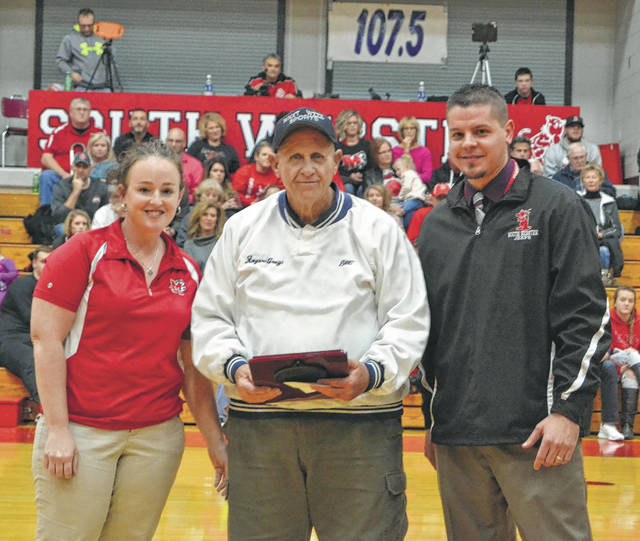 In this 2017 photograph, the athletic boosters of both Minford High School and South Webster High School recognized longtime WNXT broadcaster Roger Gray. Pictured with Gray are Minford High School Athletic Director Kristin Ruby (left) and South Webster High School Athletic Director Gabe Havens (right). Gray passed away on Tuesday at the age of 76 and following a 38-year career with the radio station(s).