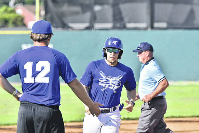 Portsmouth Post 23's Seth Nichols and coach Drew Lowe greet one another near third base during a Post 23 game earlier this season versus the Huntington Hounds.