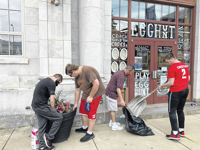 Interns from the Woodwill Summer Youth Work Experience program assist in repotting plants in front of the Southern Ohio Museum located on Gallia Street in Portsmouth near the Esplanade.