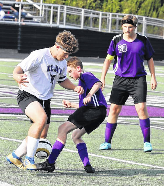 Clay's Nate Penn battles a Chesapeake Panther defender for possession of the ball during Tuesday's non-league boys soccer match at Chesapeake High School's Phil Davis Stadium. The contest was suspended in the first half due to inclement weather with the score tied at 1-1.