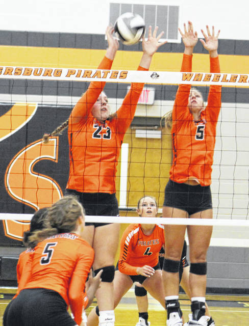 Wheelersburg's Ryleigh Meeker (12) and Kaylee Darnell (20) go up for a block during the Pirates' season-opening and Southern Ohio Conference Division II volleyball match against West on Thursday at Wheelersburg High School.
