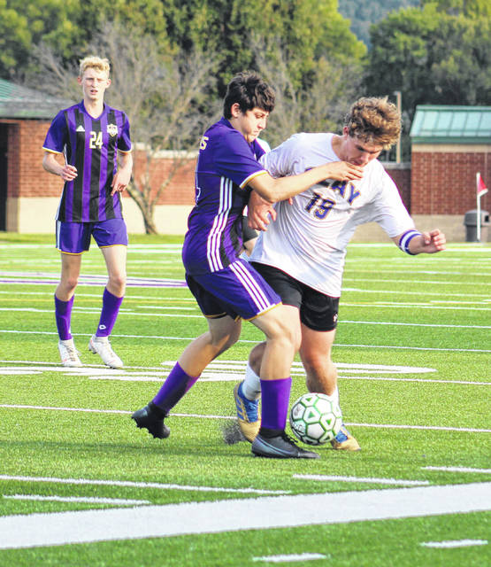 Clay senior Evan Woods (19) battles Valley's Colt Buckle (14) for possession of the ball as Valley's Bryce Stuart (24) looks on during Tuesday's Southern Ohio Conference Division I boys soccer match at Valley High School.