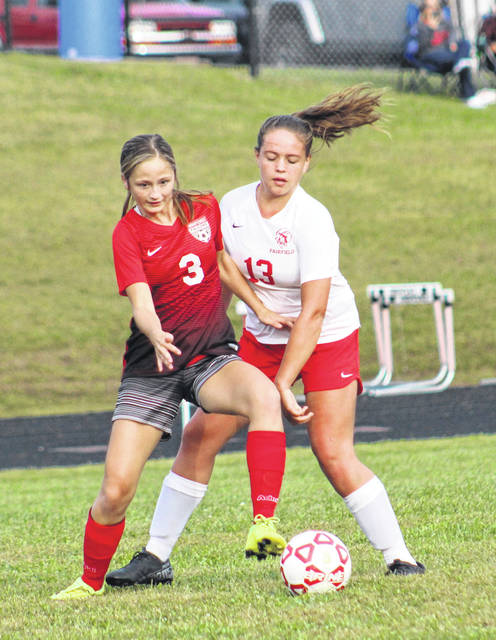 Minford's Mychal Cron (3) battles Fairfield's Kara Gleadle (13) for possession of the ball during Monday night's non-league girls soccer match at Minford High School.