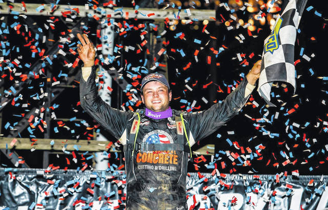 """20-year-old Hudson O'Neal lifts the checkered flag in celebration following his win in the $12,000-to-win Late Model Feature race at The Bob Miller Memorial """"River Days Rumble 50"""" hosted by Portsmouth Raceway Park."""