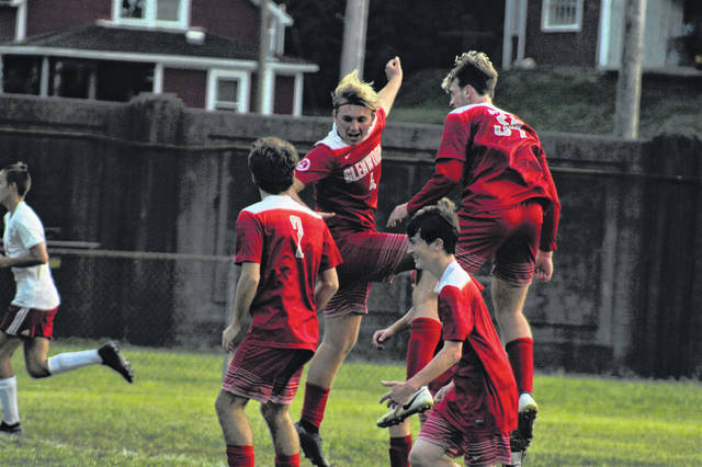 New Boston senior Tanner Voiers (4) celebrates with his teammates following his goal to cut Minford's lead in half during the Tigers' non-league contest with the Falcons on Tuesday.