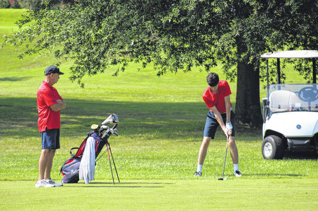 Portsmouth golf coach Buck Whitely (left) watches on as Daewin Spence (right) prepares to swing from the fairway during the Portsmouth Invitational at The Elks Country Club earlier this season. <em>File photo</em>