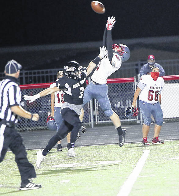 Minford's Drew Skaggs goes up to make this fourth-quarter reception over Oak Hill's Braylon Howell (3) during Friday night's Southern Ohio Conference Division II football game at Oak Hill's Davis Stadium.