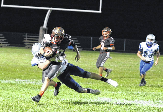 East sophomore Leviticus Justice attempts a tackle on Eastern running back Dillion Mattox in the Tartans' season-opening loss to the Eagles on Friday.