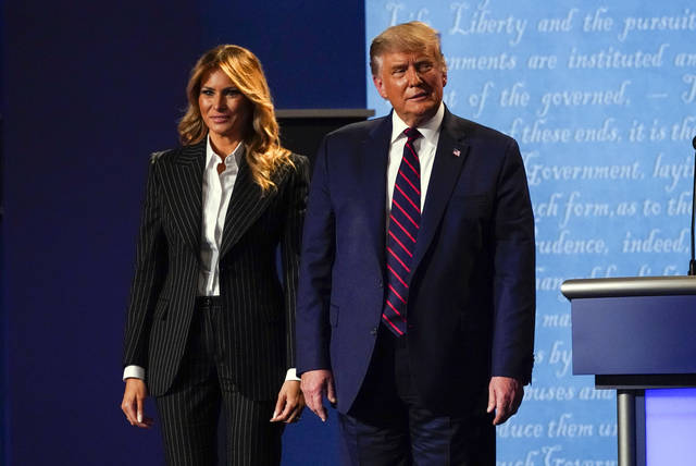 President Donald Trump stands on stage with first lady Melania Trump after the first presidential debate with Democratic presidential candidate former Vice President Joe Biden Tuesday, Sept. 29, 2020, at Case Western University and Cleveland Clinic, in Cleveland, Ohio. President Trump and first lady Melania Trump have tested positive for the coronavirus, the president tweeted early Friday. (AP Photo/Julio Cortez)