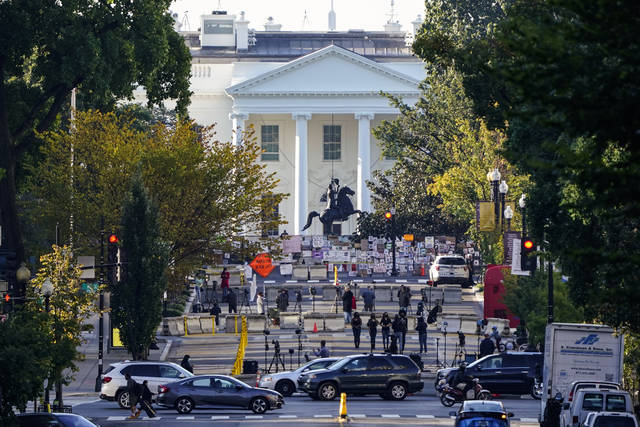 The White House is seen in Washington, early Tuesday, Oct. 6, 2020, the morning after President Donald Trump returned from the hospital where he was treated for COVID-19. Traffic moves along K Street NW as TV crews set up in Black Lives Matter Plaza. (AP Photo/J. Scott Applewhite)
