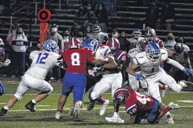 Portsmouth's Alberto Poxes (22) and Brenden Truett (8) wrap up Gallia Academy senior James Armstrong (3) during the Trojans' Ohio Valley Conference football game versus the Blue Devils at Trojan Coliseum.