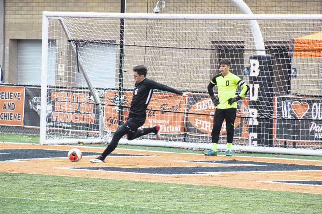 Wheelersburg senior Logan Davis (6) performs a goal kick beside senior goalkeeper Eric Green (0) during the Pirates' 1-0 win over Valley on Saturday in a Division III district semifinal at Ed Miller Stadium.
