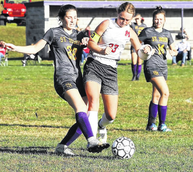 Minford senior Megan Johnson (23) battles Ironton St. Joseph defender Lydia Anderson (20) for possession of the ball during Monday's Southern Ohio Conference girls soccer match. The Lady Falcons and host Lady Flyers played to a 3-3 tie.