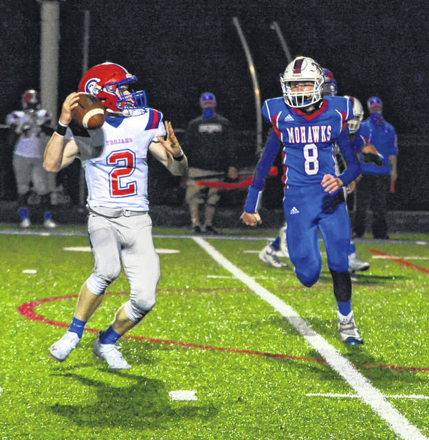 Northwest senior Chad Bowen (8) blitzes Portsmouth quarterback Drew Roe (2) during Saturday night's Division V Region 19 football playoff game at Northwest High School's Roy Rogers Field.