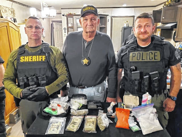 Pike County Sheriff James E. Nelson (center) with two of his deputies behind some of the drug bust finds.