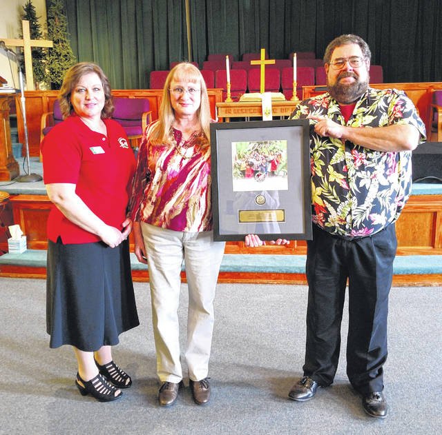 Left to Right: Sherrie Klingaman, Operation Christmas Child Southern Ohio Area Coordinator, Trish Shaffer, Nauvoo UMC Drop Off Team Leader, Pastor Pete Shaffer, Pastor, Nauvoo UMC Photos were taken at Nauvoo UMC on the occasion of the presentation of a Certificate of Appreciation to Nauvoo UMC, from Samaritan's Purse, for their 10 years of service as a shoebox Drop-Off site. (This set of photos were taken pre-COVID-19, hence no masks nor social distancing.)