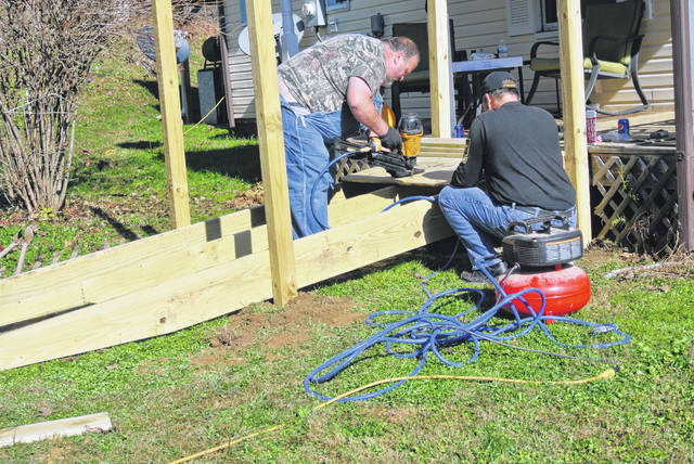 Todd Dunn (left) and Mike Bell (right) hard-at-work building a ramp for a West Portsmouth Navy veteran on Thursday, Nov. 12. Photo by Patrick Keck.