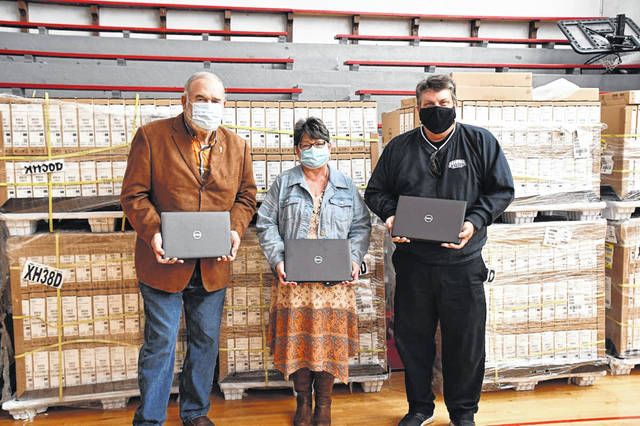 The Scioto County Commissioners (Mike Crabtree, Cathy Coleman, and Bryan Davis) standing next to more than 1,000 laptops purchased for local schools.