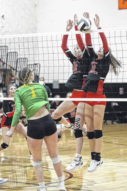 South Webster junior Faith Maloney (left) and senior Gwen Messer (right) attempt a block during the Lady Jeeps' four-set loss to Newark Catholic in a Division IV regional final played at New Lexington High School.