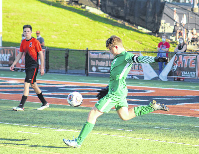 Wheelersburg senior goalkeeper Eric Green punts the ball away as fellow senior Logan Davis looks on during the Pirates' Division III regional championship soccer match against Grandview Heights on Saturday.