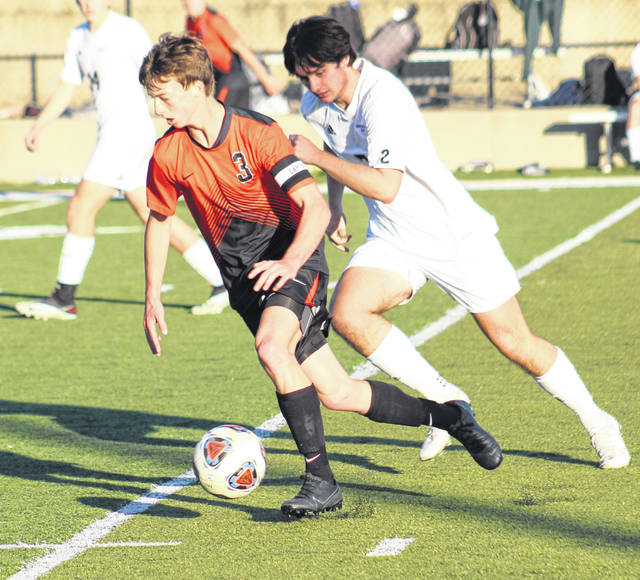 Wheelersburg senior Aaron Jolly (3) maintains possession past a Grandview Heights defender during Saturday's Division III boys soccer regional championship match at Wheelersburg's Ed Miller Stadium.