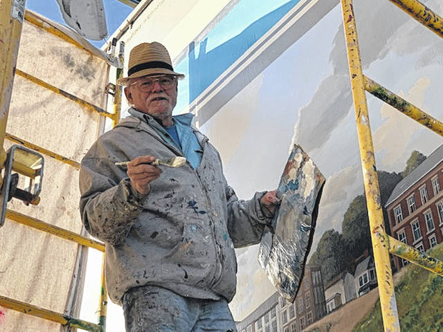 Robert Dafford, artist for the Portsmouth Murals putting some more finishing touches to the Steamboat scene on the Riverfront.