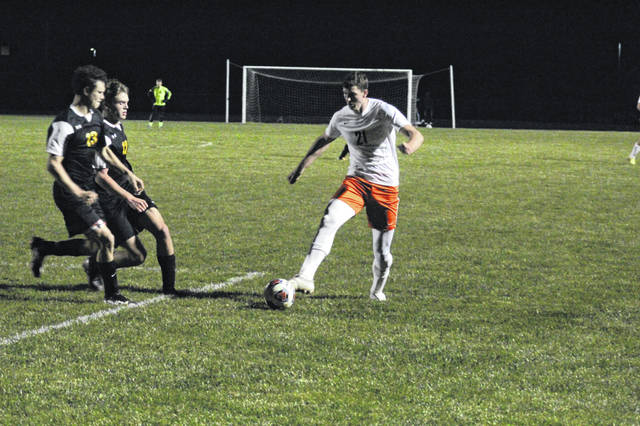 Wheelersburg senior Carter McCorkle (21) is charged by two Mustang defenders during the Pirates' 2-1 win over Lynchburg-Clay in a Division III regional semifinal.