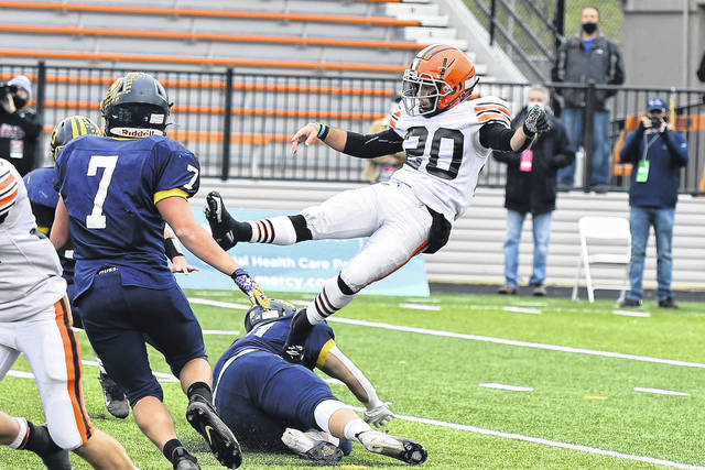 Ironton punter Kyle Howell (20) is ran into by a Kirtland defender during the first half of Saturday's Division V state championship football game at Massillon Paul Brown Tiger Stadium.