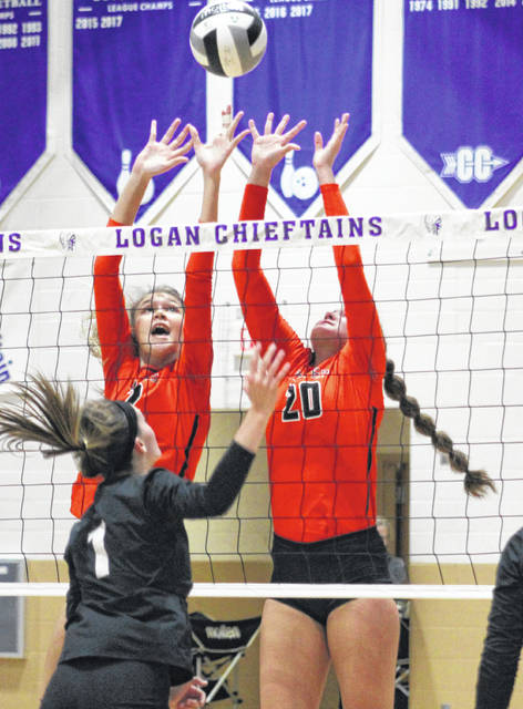 Wheelersburg's Kylee Barney (12) goes up for a block along with former teammate Mallory Bergan (20) during the Pirates' Division III regional championship volleyball match against Hiland in November of 2019 at Logan High School.