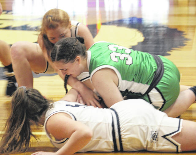 Green senior Charli Blevins (33) and Notre Dame's Charlee Lansing (top) and Mollie Creech battle for possession of the ball during Thursday night's Southern Ohio Conference Division I girls basketball game at Notre Dame High School.