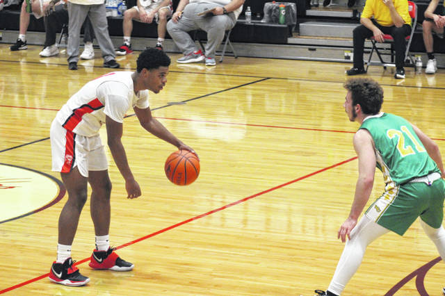 New Boston senior De'Von Jones (0) dribbles at the top of the three-point line in the Tigers' 70-37 win over West Union inside Homer Pellegrinon Gymnasium.
