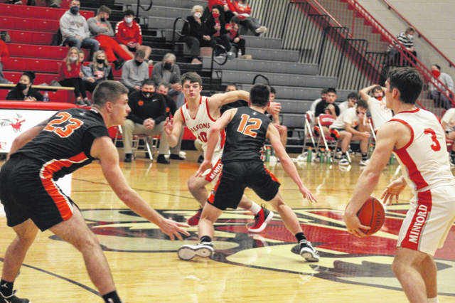 Wheelersburg seniors Gage Adkins (23) and Matthew Miller (12) defend Minford seniors Elijah Vogelsong-Lewis (3) and Matthew Risner (10) during the Pirates' 42-34 road win over the Falcons in boys Southern Ohio Conference Division II play.