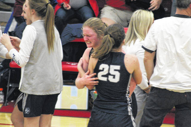 Notre Dame's Claire Dettwiller embraces Lauren Campbell (25) following the Lady Titans' 36-30 win over Peebles in a Division IV regional semifinal played at Jackson High School.