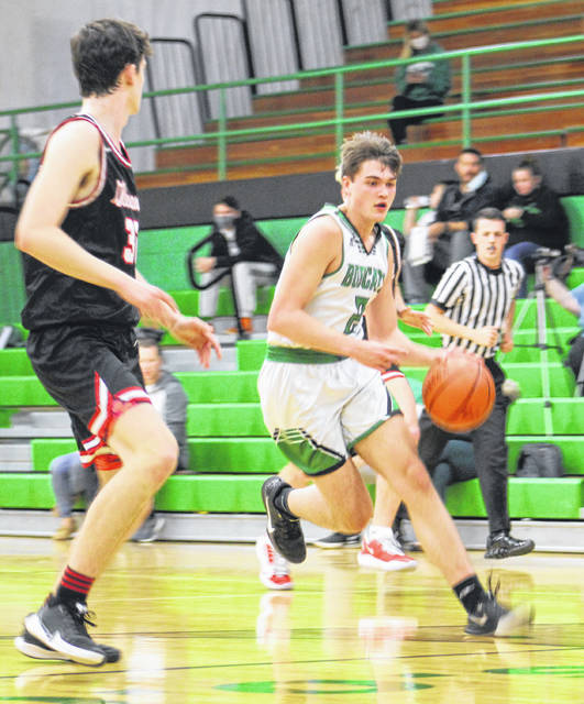 Green's Levi Sampson, defended by New Boston's Chase Clark, scored a game-high 32 points in the Bobcats' 102-75 Southern Ohio Conference Division I boys basketball defeat to the Tigers on Friday.