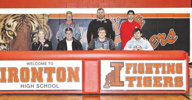 Ironton High School senior Reid Carrico, seated second from right, announces his intention and signs his national letter-of-intent to play college football for Ohio State University. Seated with Carrico are, from left, mother Shelley Carrico, father Gary Carrico and brother Garrett Carrico; standing are, from left, uncle Mike Carrico, Ironton High School head football coach and athletic director Trevon Pendleton and cousin Christopher Collins.