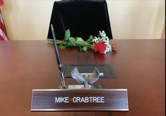 an empty chair with flowers and Mike Crabtree's nameplate sat at the table during a Scioto County Commissioners meeting