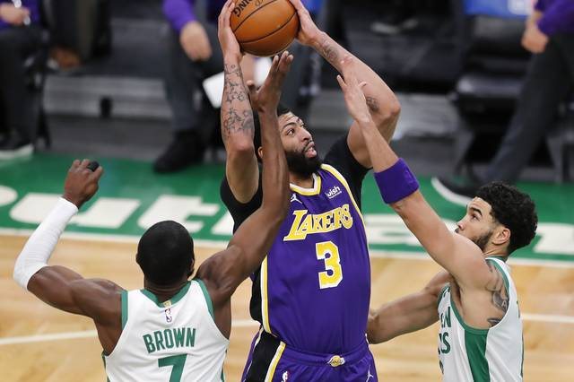 Los Angeles Lakers' Anthony Davis (3) shoots between Boston Celtics' Jaylen Brown (7) and Jayson Tatum during the first half of an NBA basketball game Saturday, Jan. 30, 2021, in Boston. (AP Photo/Michael Dwyer)
