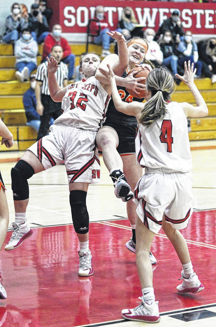 South Webster's Bella Claxon (32) and Wheelersburg's Lyndsay Heimbach (24) get tangled up for a loose ball during Monday night's Southern Ohio Conference Division II girls basketball game at South Webster High School.