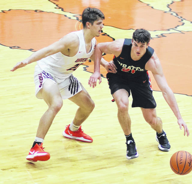 Wheelersburg's Carter McCorkle (21) looks to drive past Waverly's Zeke Brown (22) during Tuesday night's Southern Ohio Conference Division II boys basketball game at Waverly's Downtown Arena.